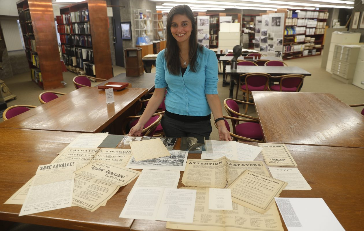 Niagara Falls Local History Librarian Courtney Geerhart has assembled a display marking the 90th anniversary of the annexation of the Village of LaSalle into the City of Niagara Falls 90 years ago. She has assembled full-page newspaper ads, handbills and other materials showing how high tensions ran.  (John Hickey/Buffalo News)