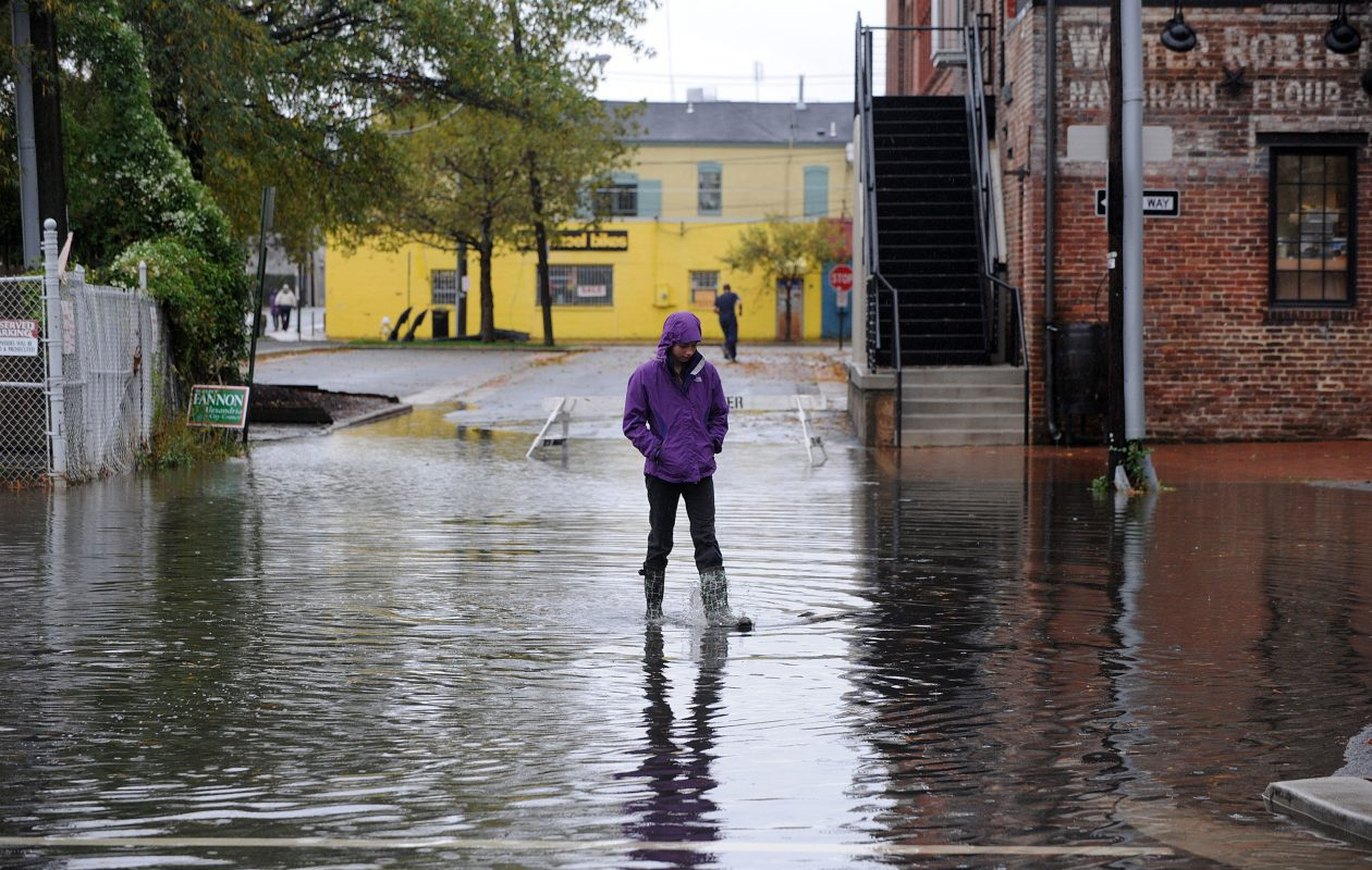 Pedestrians navigate through flooded downtown Alexandria following Hurricane Sandy's track through the nation's capital Oct. 30, 2012, in Virginia. According to Don Paul,  this environmental problem is not going to get any better. (Olivier Douliery/TNS)