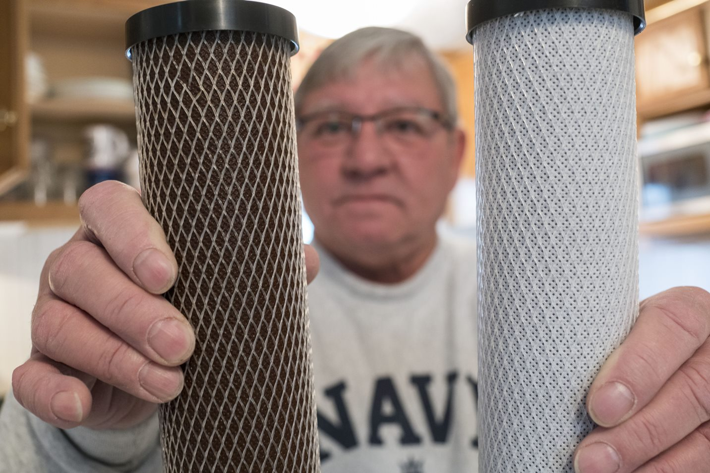 Raymond Becker holds a water filter that has been discolored from 30 days of use, left, and a new, unused water filter, right, for comparison in the kitchen of his home in Circle Courts Mobile Home Park on Saturday, May 6, 2017.  (Derek Gee/Buffalo News)