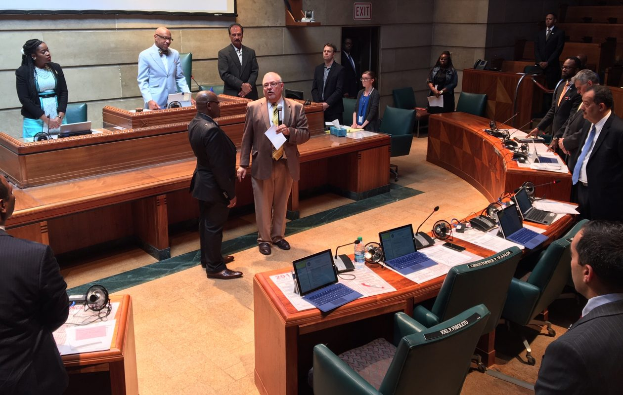 Bishop John Paul Chea of Liberia (in black) on floor of Common Council Chambers with  Chaplain Rev. Al Warner