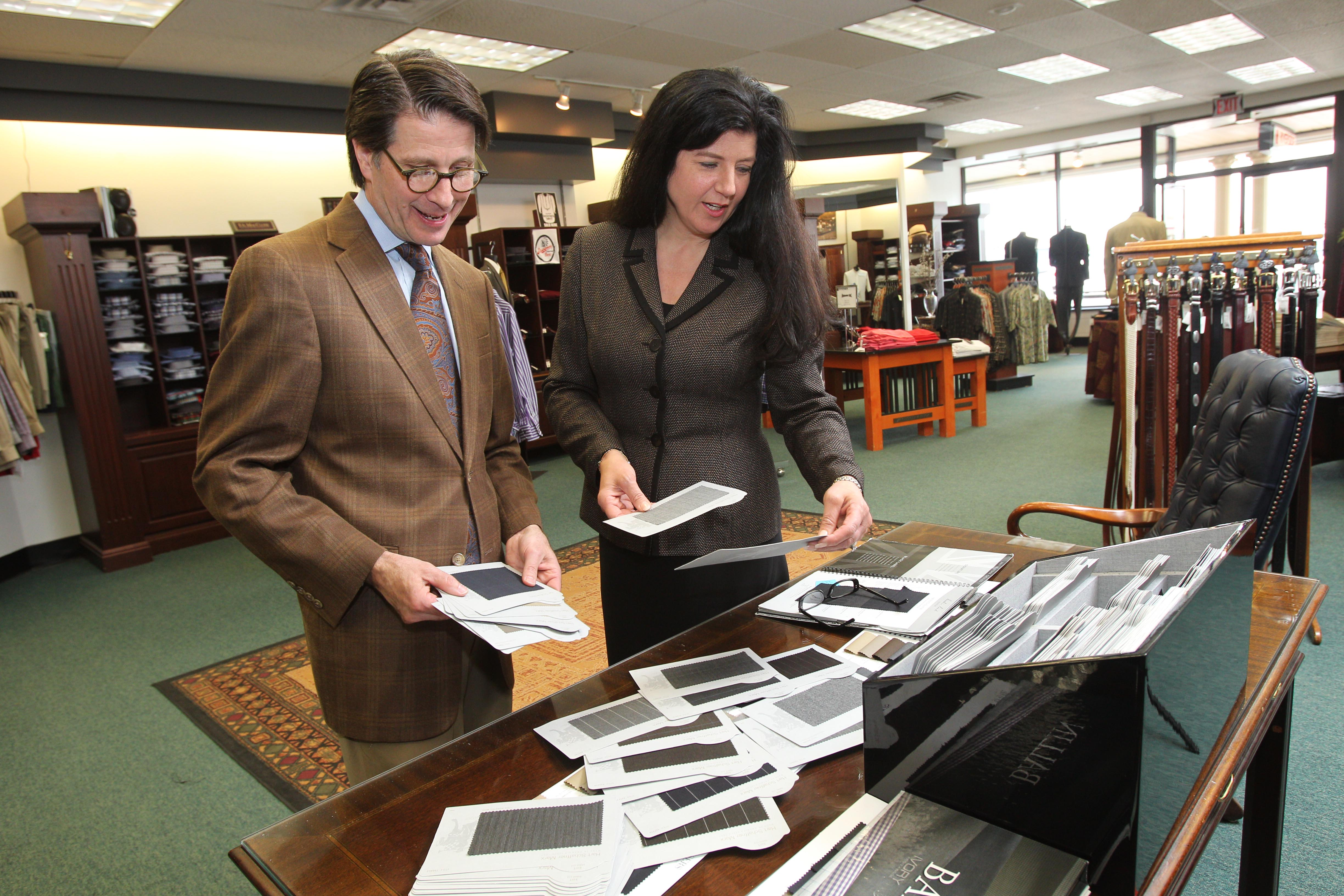 Natalie Neumann, co-owner of Riverside Men's Shop in the Northtown Plaza in Amherst.  She chooses fabric swatches for the fall order with buyer Joe Jacobi, left,.  {Photo by Sharon Cantillon / Buffalo News}