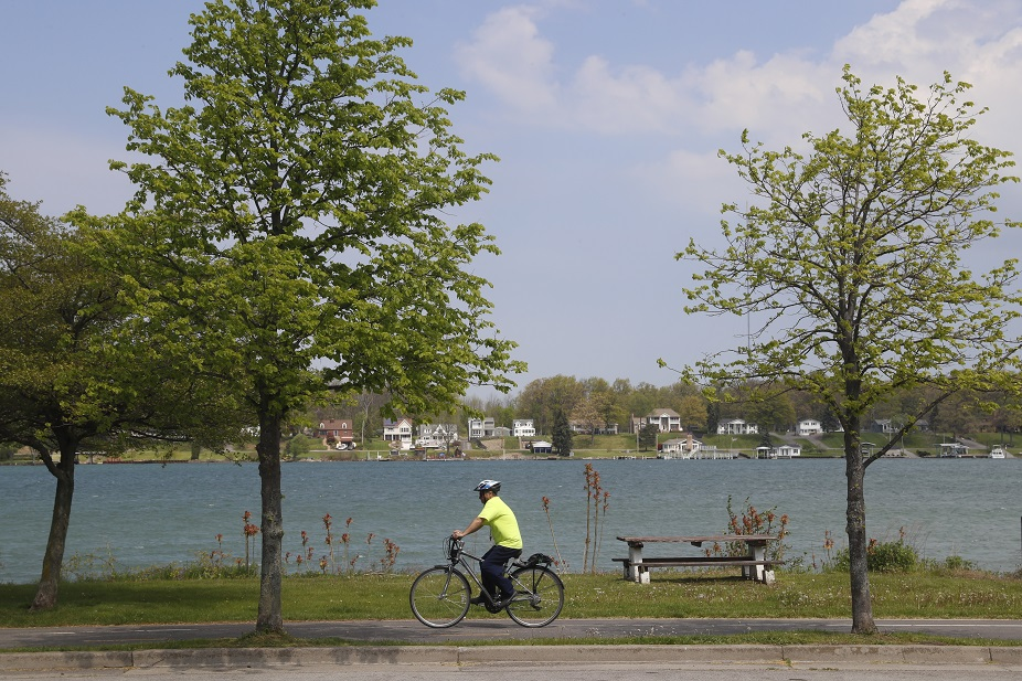 A bicyclist rides in Isle View Park in the Town of Tonawanda on a warm Wednesday. Warm temperatures are expected Thursday with the possibility of severe thunderstorms.(John Hickey/Buffalo News)
