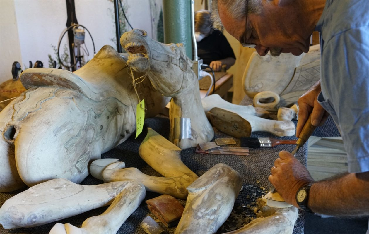 Volunteer woodcarver Jim Ronan carves a new foot to replace a missing portion of one of the horses for the 1924 carousel. (Derek Gee/Buffalo News)