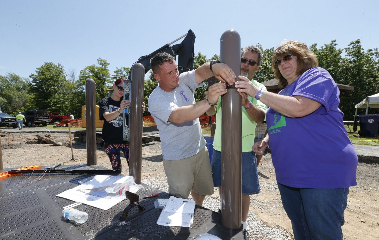Army Staff Sgt. Troy A. Springer, center, with his wife Hayley, left, install posts for a new playground in Amherst's Billy Wilson Park, named in honor of the soldier from Amherst killed in Afghanistan in 2012. Wilson's parents, Bill and Kim, are pictured at right. Photo by Robert Kirkham / Buffalo News.