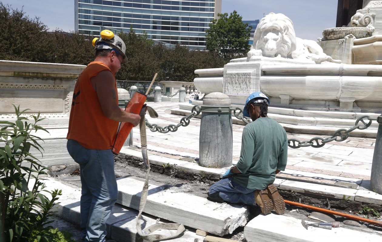 Tony Harris, a stonemason, right, and Mike McGary, a laborer, work on the McKinley Monument steps. (John Hickey/Buffalo News)