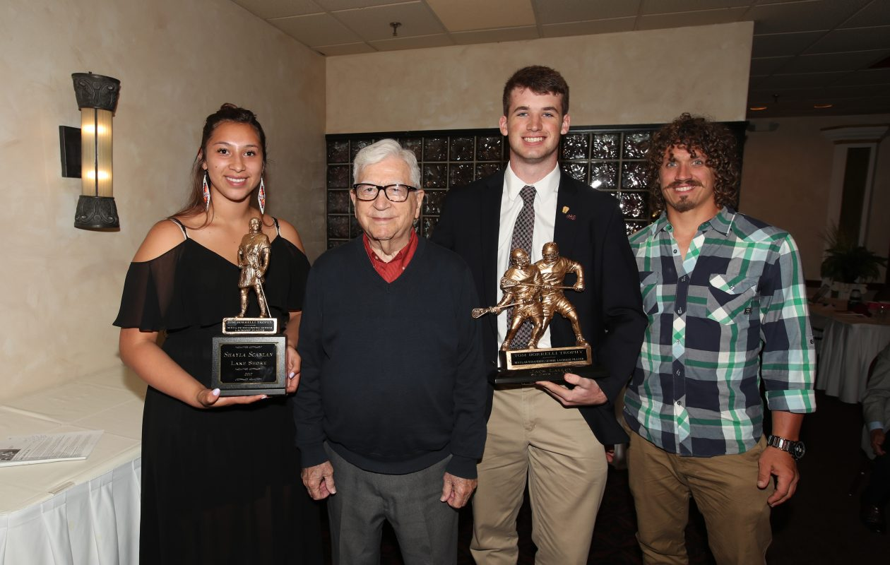 Lake Shore's Shayla Scanlan (far left) and St. Joe's Jack Lalley (second from right) are the newest Tom Borrelli Memorial Award winners. They accepted their awards alongside George Borrelli and Buffalo Bandit Mark Steenhuis at Ilio DiPaolo's on Monday. (James P. McCoy/Buffalo News)