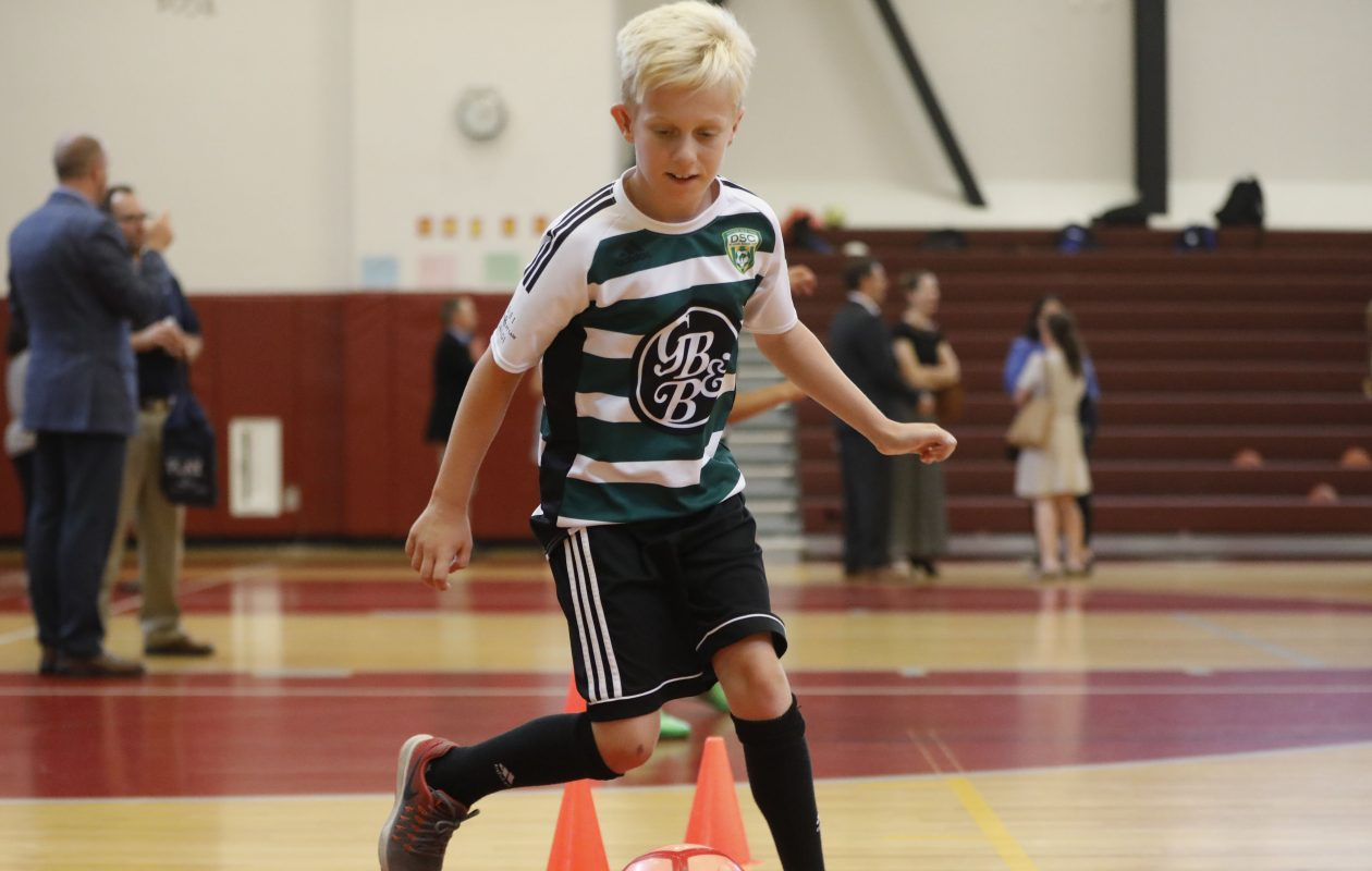 Liam Ainslie, 12, dribbles the ball as he and young athletes from the Delaware Soccer Club practice in the gym at City Honors School as a report was released saying more Western New York kids need more such opportunities to play sports. (Derek Gee/Buffalo News)