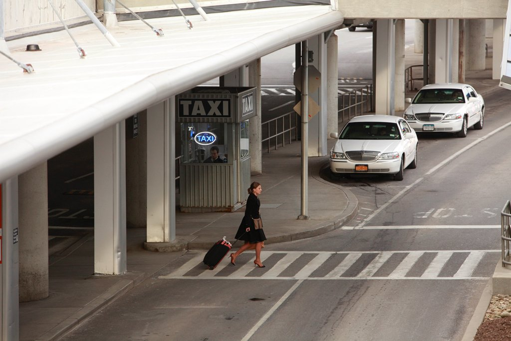 A traveler crosses the street near a taxi stand at the Buffalo Niagara International Airport in this file photo. Travelers using ride-hailing service to or from the airport will be charged $3.50. {Derek Gee/Buffalo News}