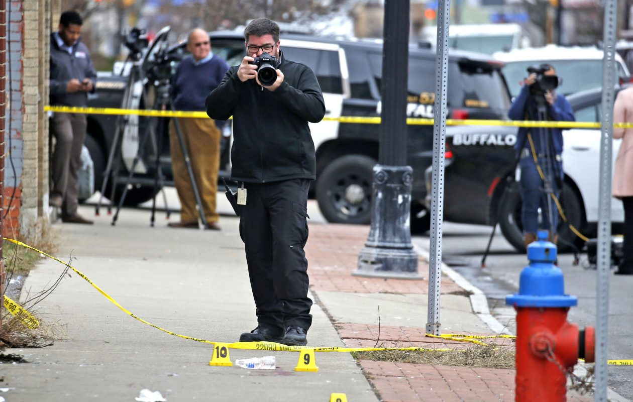 Buffalo Police photographer Andy Nostrant takes pictures of spent hand-gun shells that were littered at the scene of a triple shooting on Genesee Street and Eller Avenue on Buffalo's east side on Monday, March 6, 2017.  (Robert Kirkham/Buffalo News)