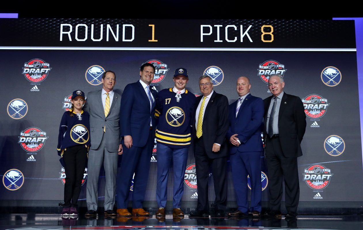 Casey Mittelstadt, center, poses with the daughter of Sabres assistant scouting director Jerry Forton, coach Phil Housley, General Manager Jason Botterill, owner Terry Pegula, head amateur scout Jeff Crisp and Kevin Devine, the director of player personnel. (Getty Images)
