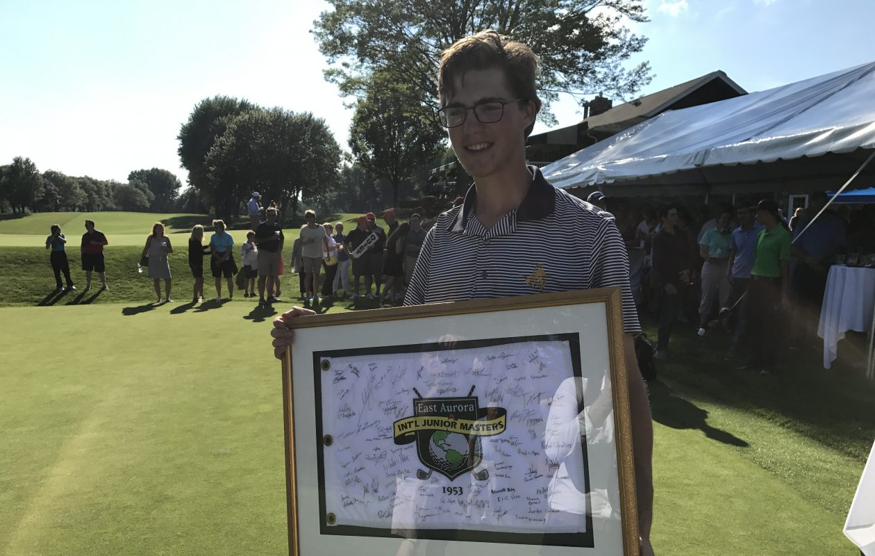 Danny Gianniny holds a framed flag signed by all 80 participants after winning the International Junior Masters. (Matt Schneidman/The Buffalo News)