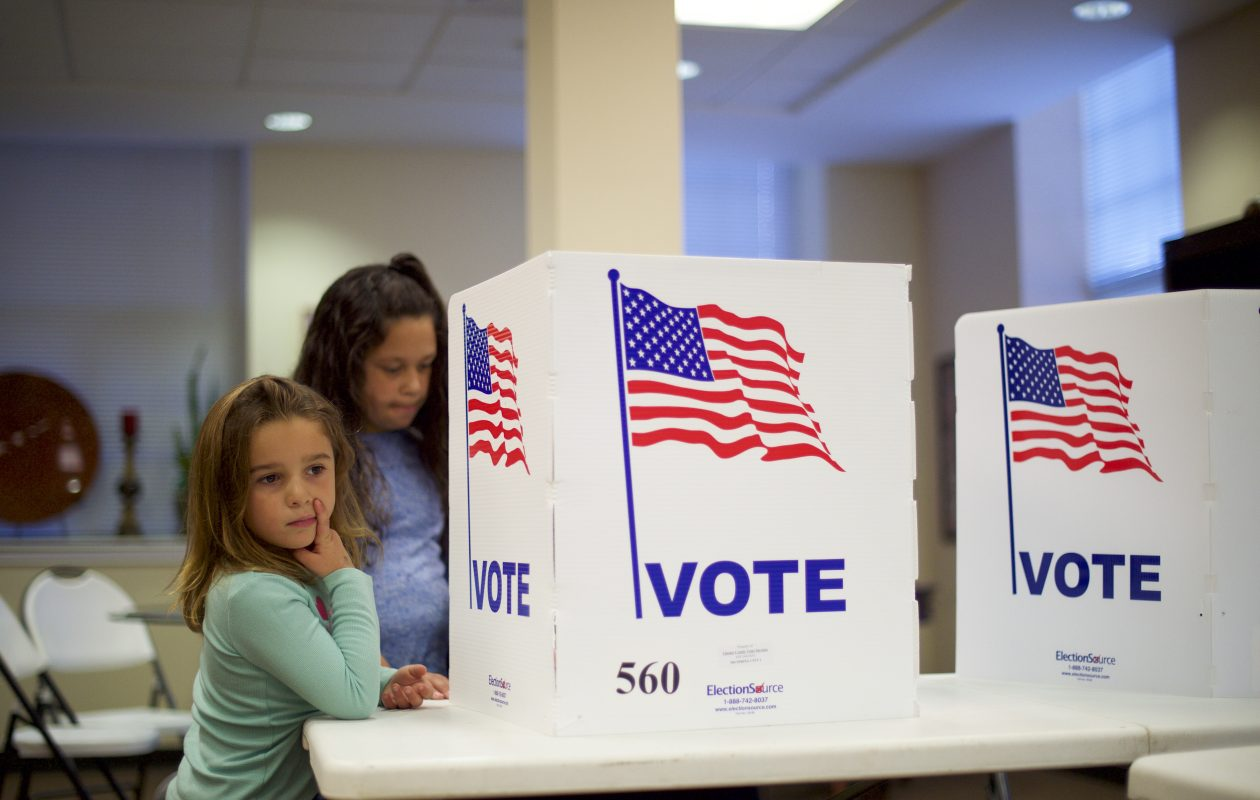Angelina Blewitt, 5, left, and her sister, Mackayla, 9, watch as their mother, Bridget, votes in Spring City, Pa., on Nov. 8, 2016. (Mark Makela/The New York Times)