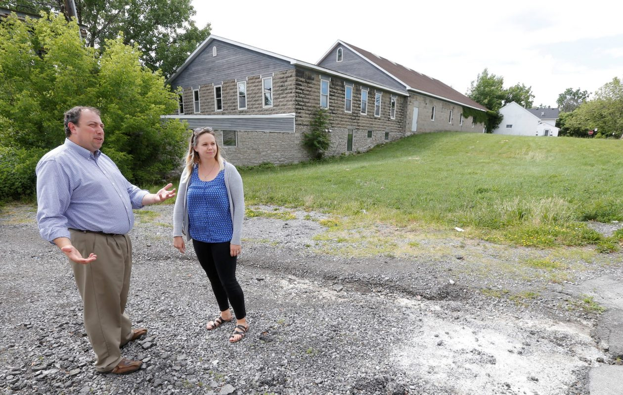 Williamsville Mayor Brian Kulpa, left, and Community Developement Director Maggie Hamilton stand outside the former Erie County Cooperative Brewery building on West Spring Street in  Williamsville on Tuesday, June 20, 2017. The village is seeking a $10 million state grant to purchase and renovate the building, which village officials hope can house a microbrewery and artists' galleries. (Robert Kirkham/Buffalo News)