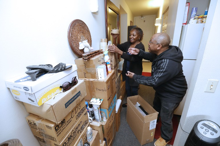Carmen Brooker, left, and fellow resident James Graham pack her belongings at the subsidized Shoreline Apartments, which are being replaced.  She just got into an SA+A development on Best Street; Graham was not so lucky, ending up on a waiting list. (Robert Kirkham/Buffalo News)