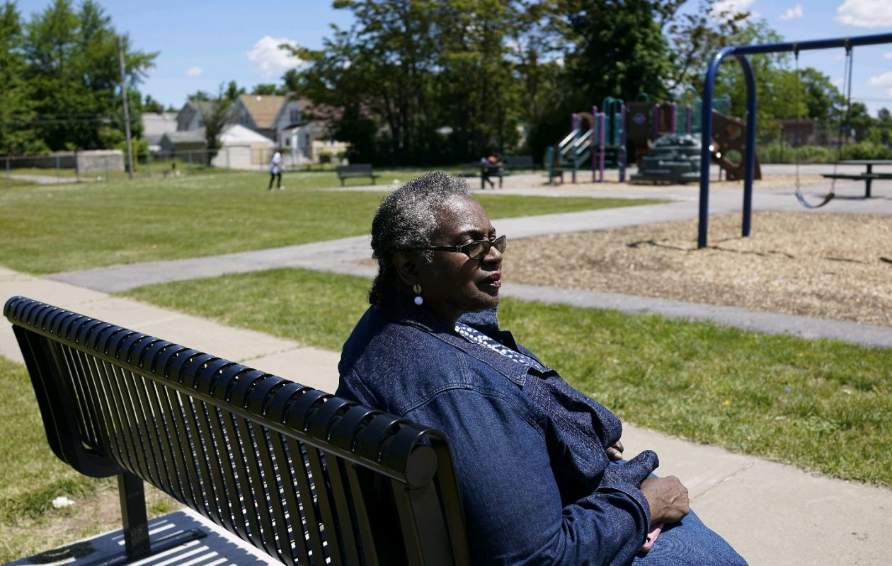 Della Miller sits on one of the Dewey Park benches she got installed through participatory budgeting. She discovered the need years ago when trying to keep an eye on her son on the playground. (Derek Gee/Buffalo News)
