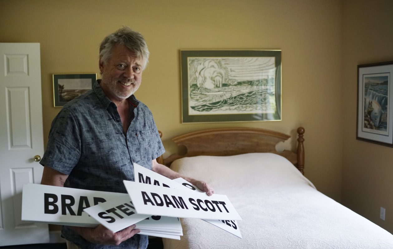 Craig Avery sorts through some of the scoreboard names he has collected of young golfers who have stayed at his Lewiston home during the Porter Cup over the years. (Derek Gee/Buffalo News)