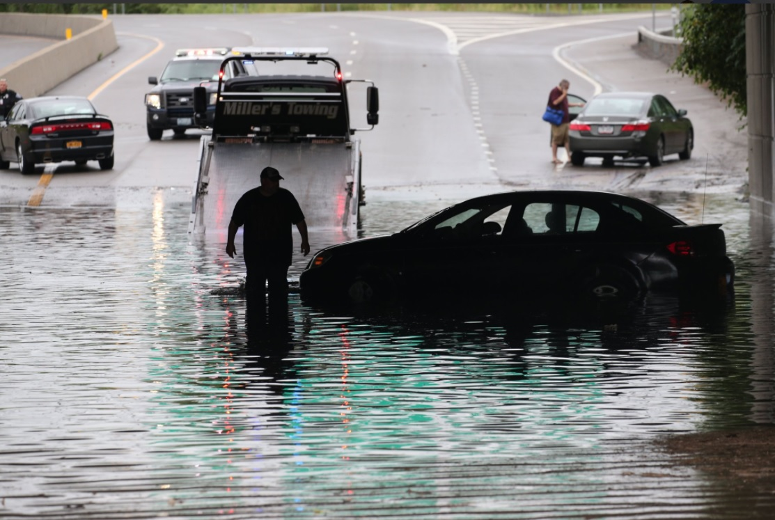 A tow truck operator wades through standing water on the Kensington Expressway to recover a disabled car beneath Genesee Street. (Derek Gee/Buffalo News)