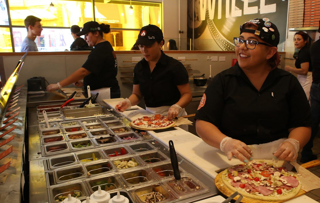 Customers watch as their pizza is being prepared as customers watch at Blaze Pizza in Pasadena, Calif. on July 19, 2016. Blaze Pizza is a fast-casual pizza chain that plans to open a location at The Boulevard in Amherst. (Glenn Koenig/Los Angeles Times/TNS)