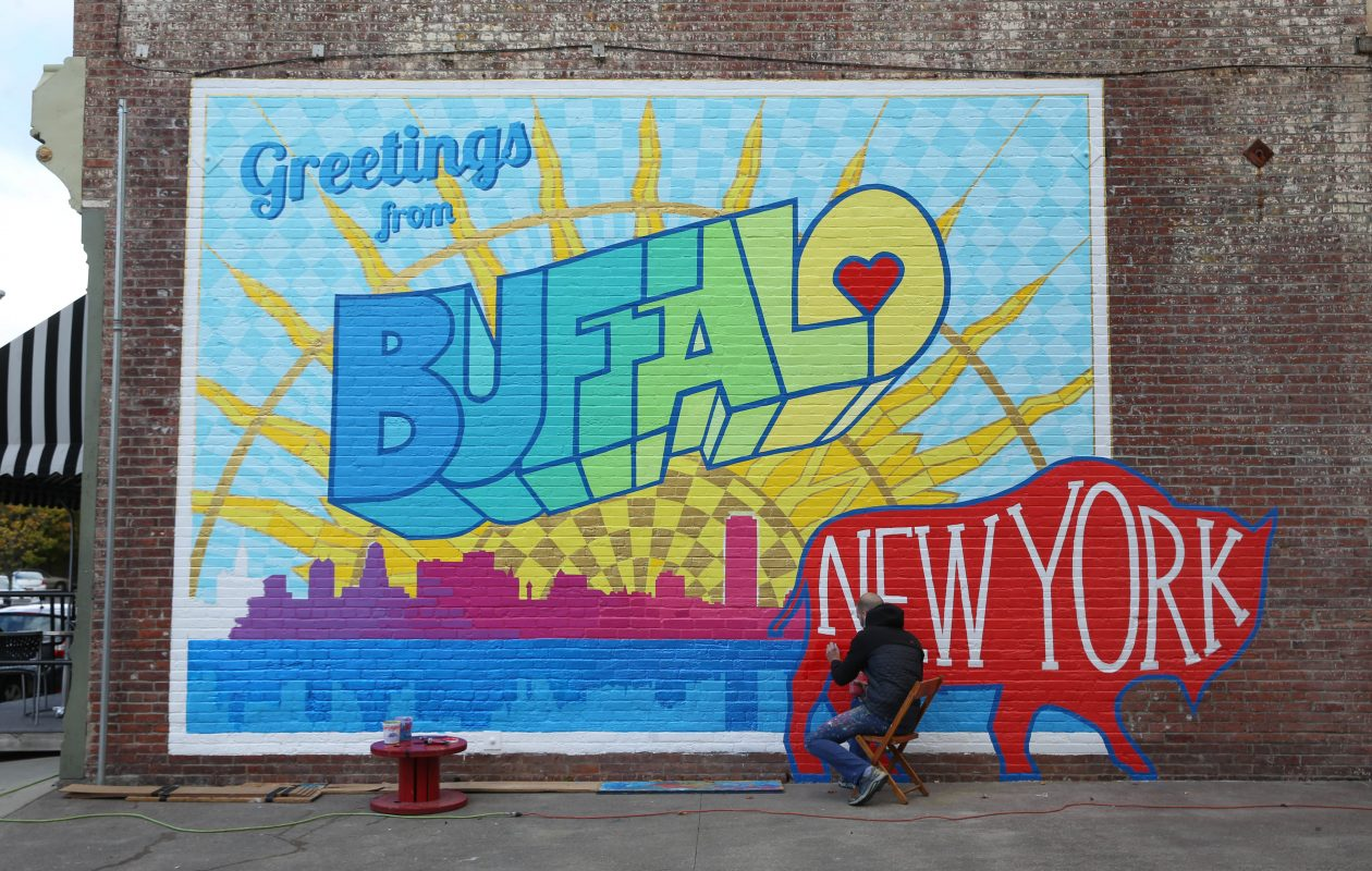 "Artist Casey William Milbrand works on his colorful ""Greetings from Buffalo"" mural in 2016.(Sharon Cantillon/Buffalo News)"