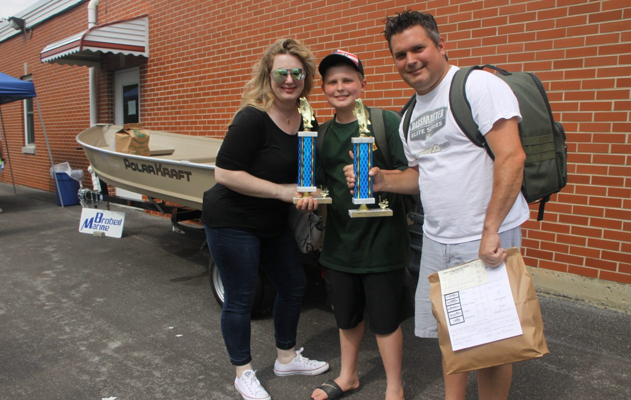 Keegan Walczak won the PolarKraft boat, motor and trailer from Brobeil Marina. Dad was sure happy!  Keegan's mom ,Jaclyn Elsen joins in the celebration.