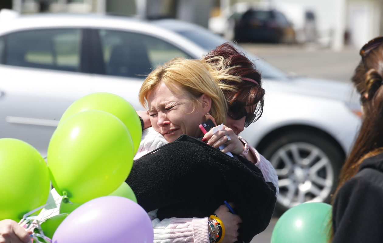 Lisa Fischer, in black sweater, is hugged by her neighbor at a 2015 memorial celebration of what would have been her son Ryan's 17th birthday.  (John Hickey/Buffalo News)