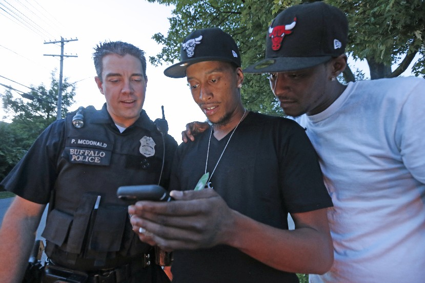 Buffalo Police Officer Patrick McDonald watches a viral video that shows him catching a long touchdown pass in a street football with Albert Woolford (center), the man who threw the pass, and Woolford's childhood friend, Tyrone Pace. (Robert Kirkham/The Buffalo News)