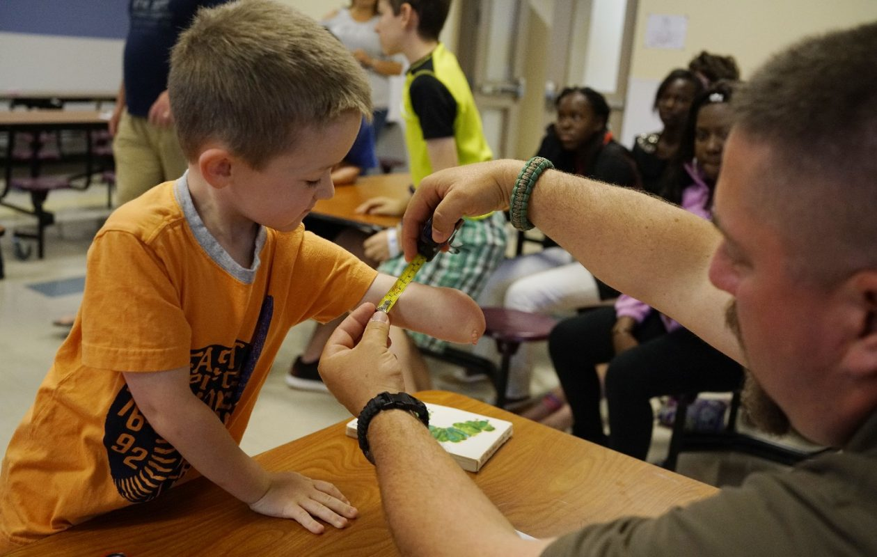 Caedan Muldoon, 4, gets measured for a new prosthetic hand by teacher Leif Johnson during a summer program at Health Sciences Charter School where students use 3-D printers to make the artificial hands. (Derek Gee/Buffalo News)