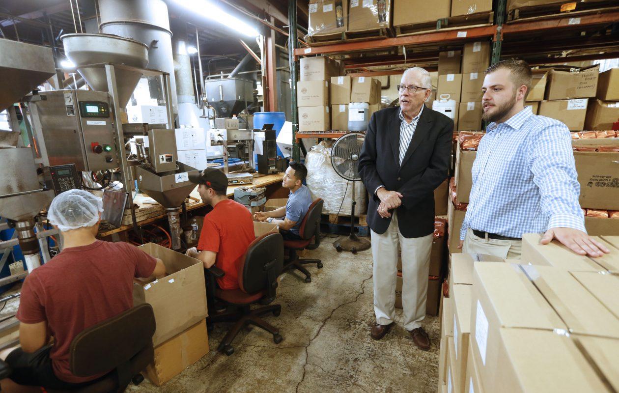 UB student Joseph Ricciardi, right, and Warren Emblidge Jr. of, chairman of McCullaugh Coffee, watch the progress at the company's Swan Street facility.  (Robert Kirkham/Buffalo News)