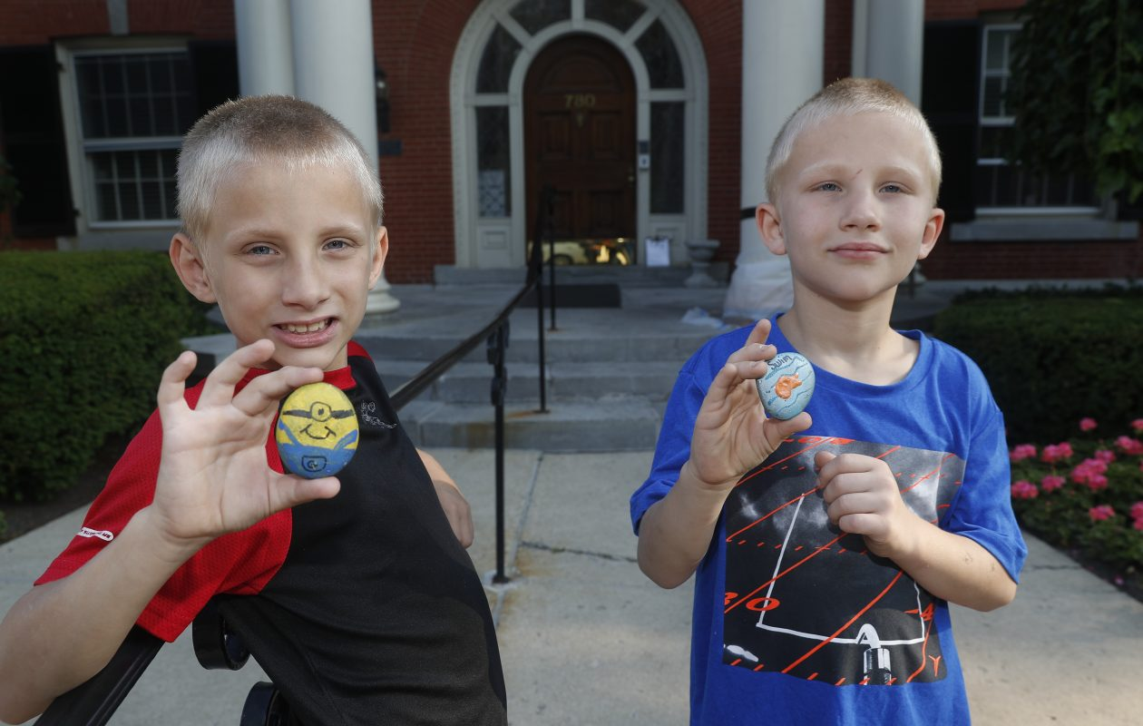 Kristina Gassman's sons, Wyatt, 8, left,  and Landin, 7, have been shuttled between relatives and just a couple of days ago came to stay with their mom at the Ronald McDonald House. They walked outside on their way to the hospital when they found two painted rocks — a minion and a fish and declared them good luck rocks for their sister. (John Hickey/Buffalo News)