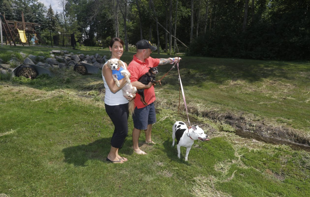 Adam and Nikki Keller with their three dogs in the backyard of their home in Clarence Center. (John Hickey/Buffalo News)
