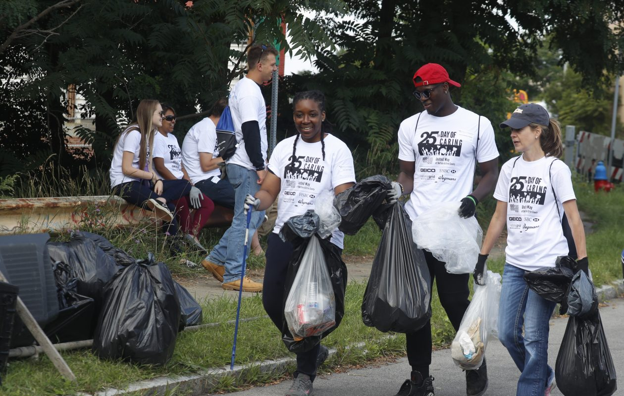 Maureen Erokwu, left, Kwame Boaky-Yiadom, and Jill Illenz from UBs MBA program carry collected trash as they cleaned up the Scajaquada Creek Bike Path on the United Way Day of Caring. (John Hickey/Buffalo News)