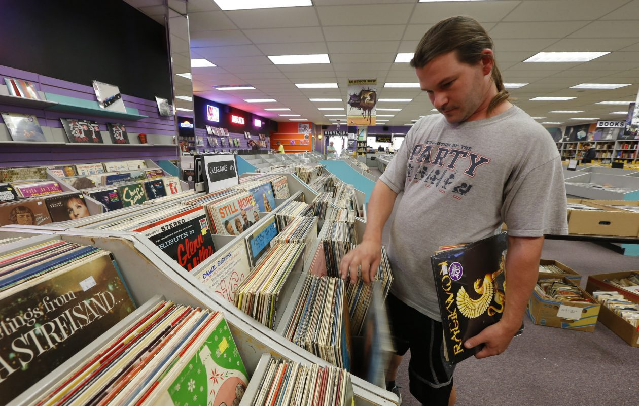 Bradley Andersen of Buffalo combs the stacks looking for hidden treasures. Record Theatre will close for good on Sunday.  (Robert Kirkham/Buffalo News)