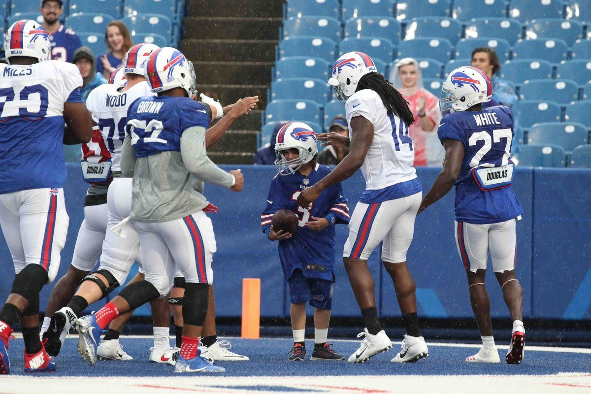 The Bills surround honorary captain Garett Rumfola after the start of practice Friday night. (James P. McCoy/Buffalo News)