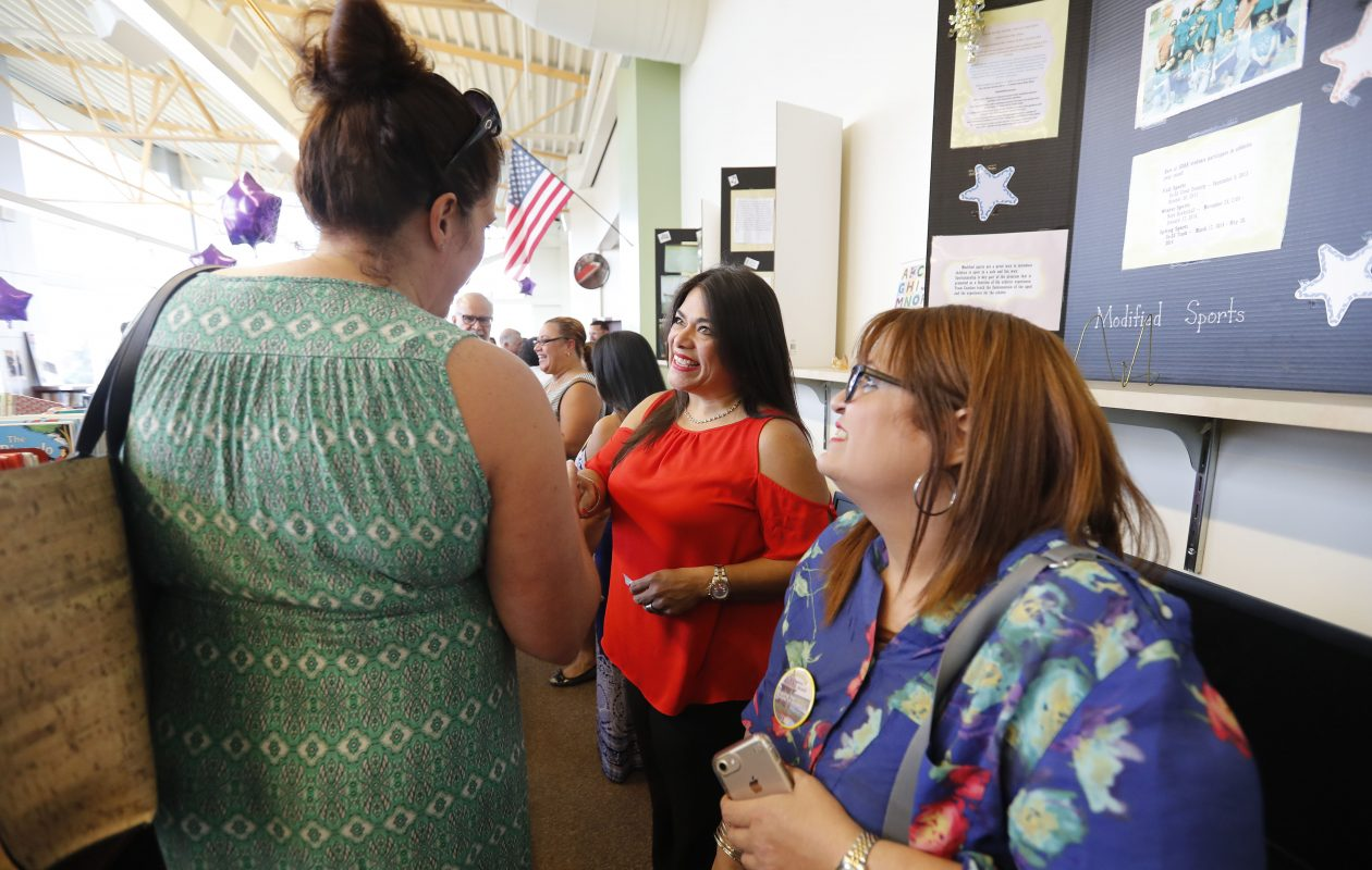 New Buffalo teachers Mares Claudio, center, and Lottie Bou, right, are greeted by Heather Maldonado, left, during a reception welcoming 9 new teachers from Puerto Rico at the Herman Vadillo Bilingual Academy in Buffalo Wednesday, August 30, 2017.            (Mark Mulville/Buffalo News)