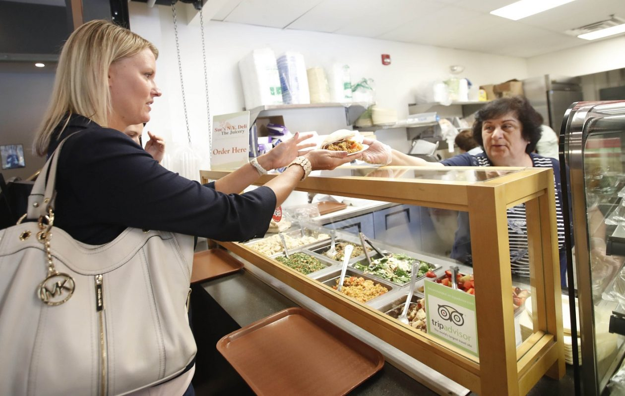 Moura Khoury, the owner's sister-in-law, right, serves Katie Schultz, a regular at Sue's Deli. (Sharon Cantillon/Buffalo News)