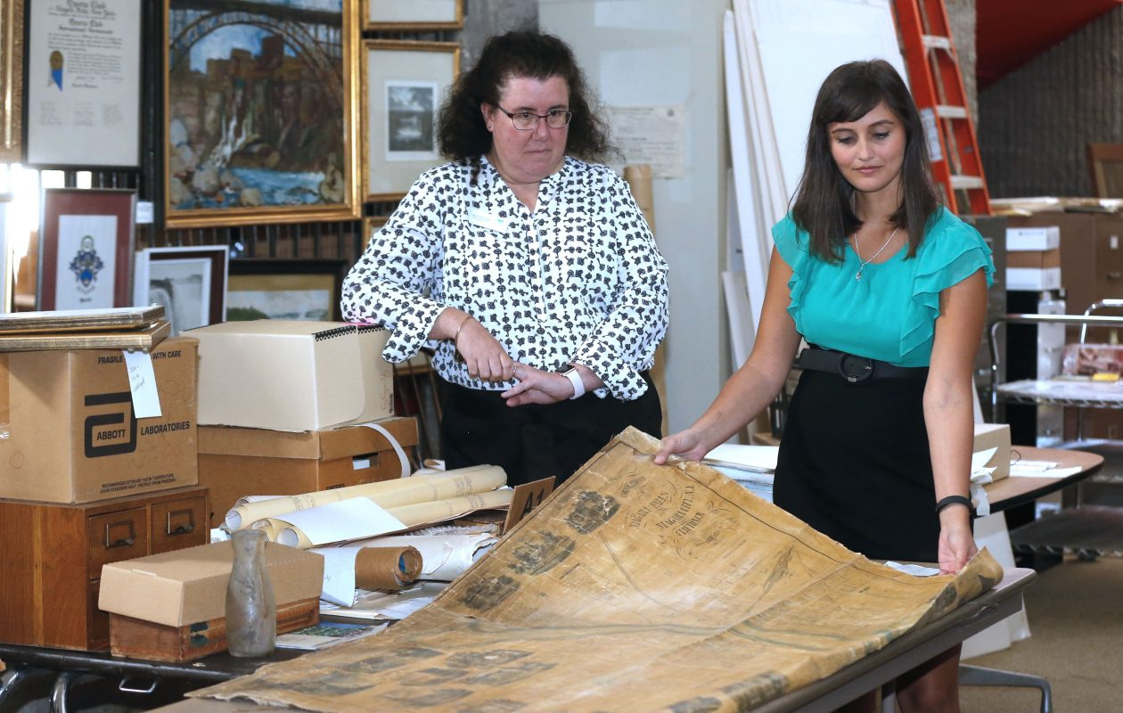 Local history librarian Courtney Geerhart, right, shows library executive director Sarah M. Potwin one of the Local History department's many maps of the city. This one is from 1857 and includes drawings of significant buildings. (Robert Kirkham/Buffalo News)