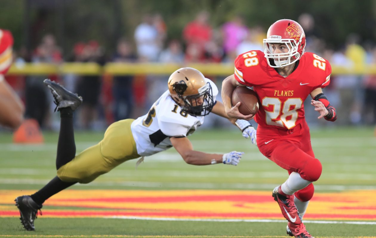 Senior running back Jake Falzone runs past Sweet Home's Vlad Kovalchuk during Williamsville East's 21-7 home win over the Panthers. (Harry Scull Jr./ Buffalo News)
