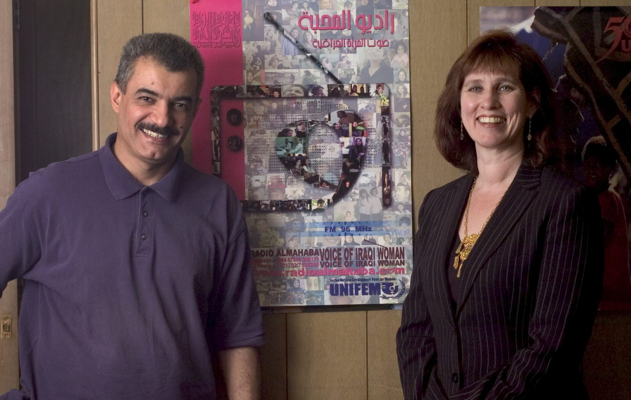 A judge has thrown out fraud charges against Debbie Bowers and Steve Shariff , shown in a file photo standing in front of the posters used to advertise the women's radio station in Baghdad. (Buffalo News file photo)