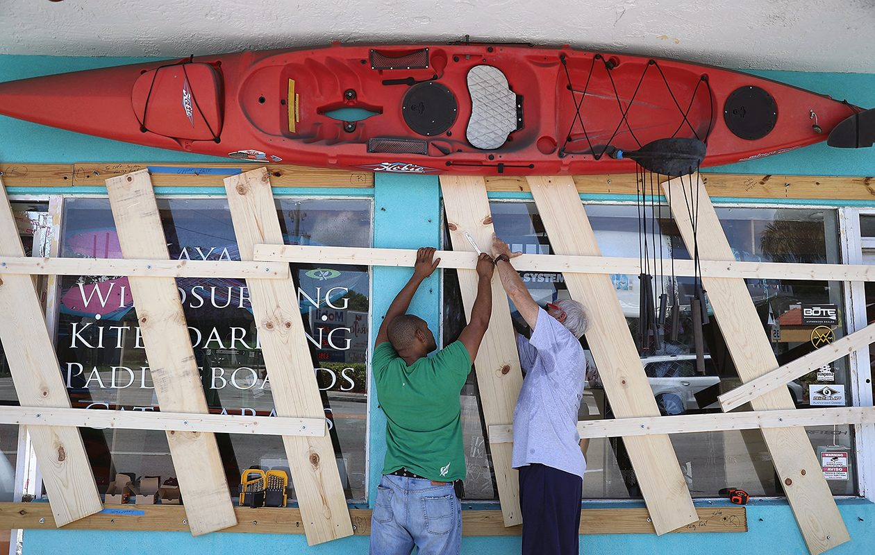 As Hurricane Irma bears down on Florida, Jim DeSilva, left, and Milton Ibanez put up boards to protect windows on their business, Sandy Point, on Sept. 7 in Miami. (Joe Raedle/Getty Images)