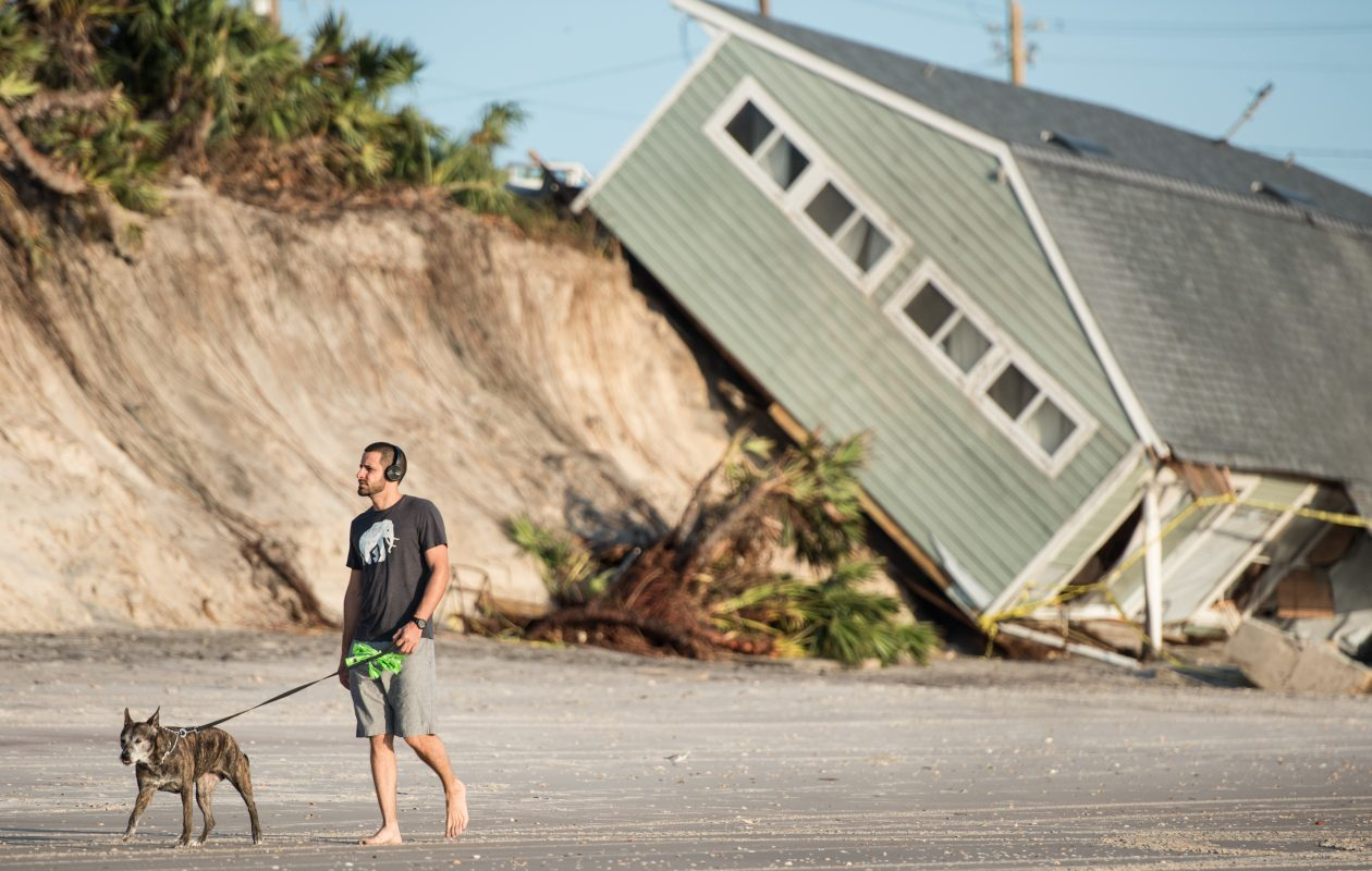 Jose Orosz walks his dog Karen by a beachfront home destroyed by Hurricane Irma on Sept. 13, 2017, in Vilano Beach, Fla. Nearly 4 million people remained without power more than two days after Irma swept through the state.  (Getty Images)