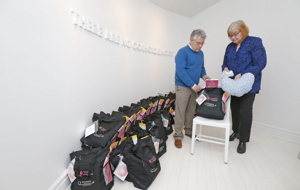 Rob Jones, executive director of the Breast Cancer Network of Western New York, with survivor Bev Jasinski, inventory gift bags that the nonprofit distributes to recently diagnosed patients from the headquarters on Walden Avenue in Depew.   (Robert Kirkham/Buffalo News)