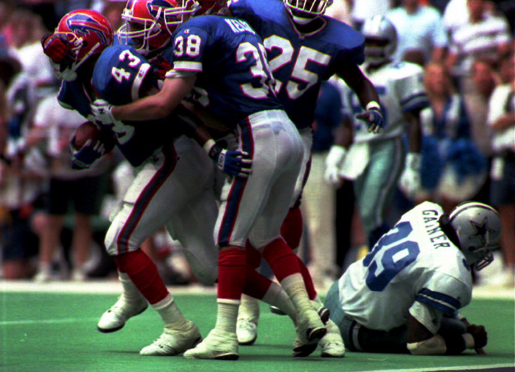 Buffalo Bills safety Matt Darby (43) is mobbed by teammates after intercepting a Troy Aikman pass with 12 seconds to go in the game as Dallas Cowboys running back Derrick Gainer (39) lies on the turf in Dallas on Sept. 12, 1993. The interception sealed a 13-10 win for the Bills.  (Tim Roberts/Getty Images)