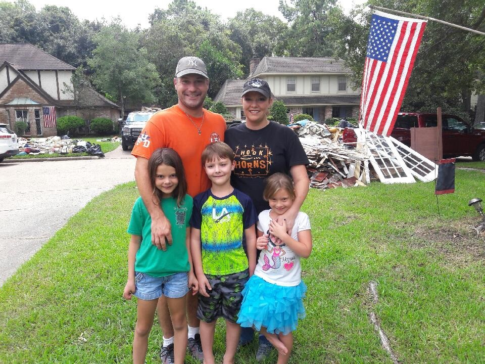 Greg and Carrie Kopacz with children Gwendolyn, 8, at left, twins Jacob and  Abigail, 6, center and right with debris from their flooded house in front of their Houston home. Their daughter Veronica, 18, was not home for the photo.  (Family photo)
