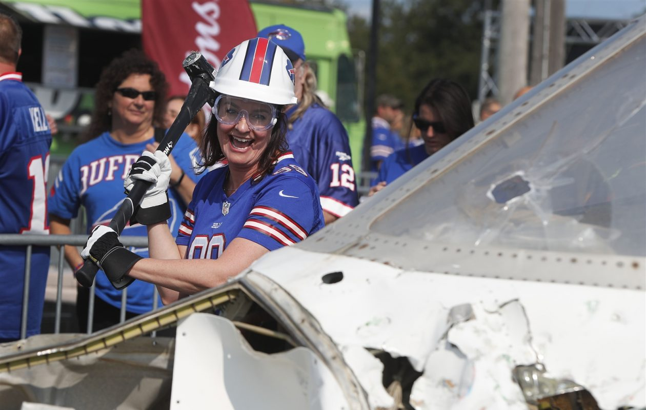 Seasons ticket holder Holly Farner from San Francisco takes a sledgehammer to a jet before the game. (Mark Mulville/Buffalo News)