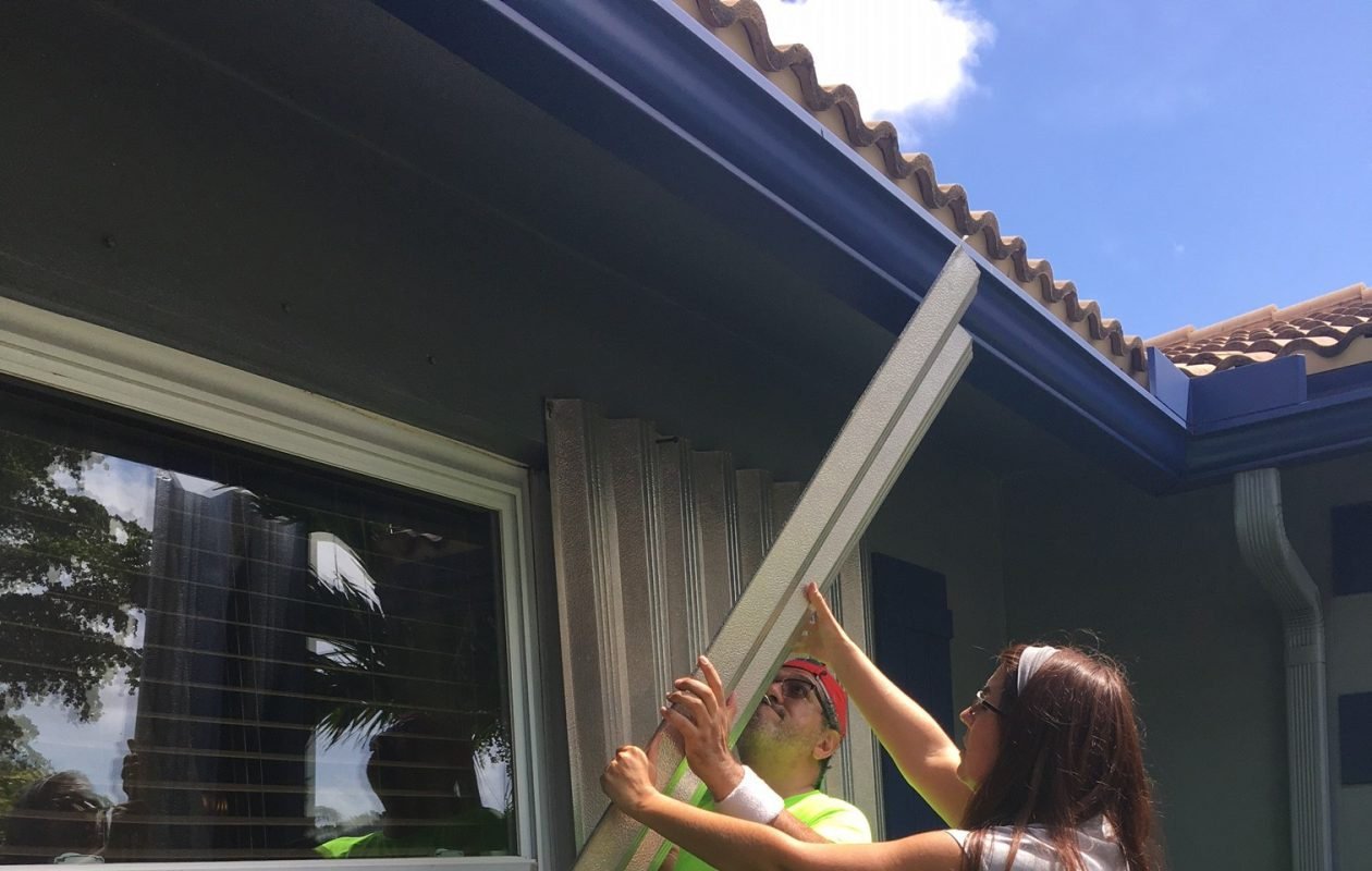 Former Amherst resident Carrie Ann Perez works with her husband to finish putting up hurricane shutters on their Boca Raton home Friday in preparation for Hurricane Irma. (Courtesy of Carrie Ann Perez)