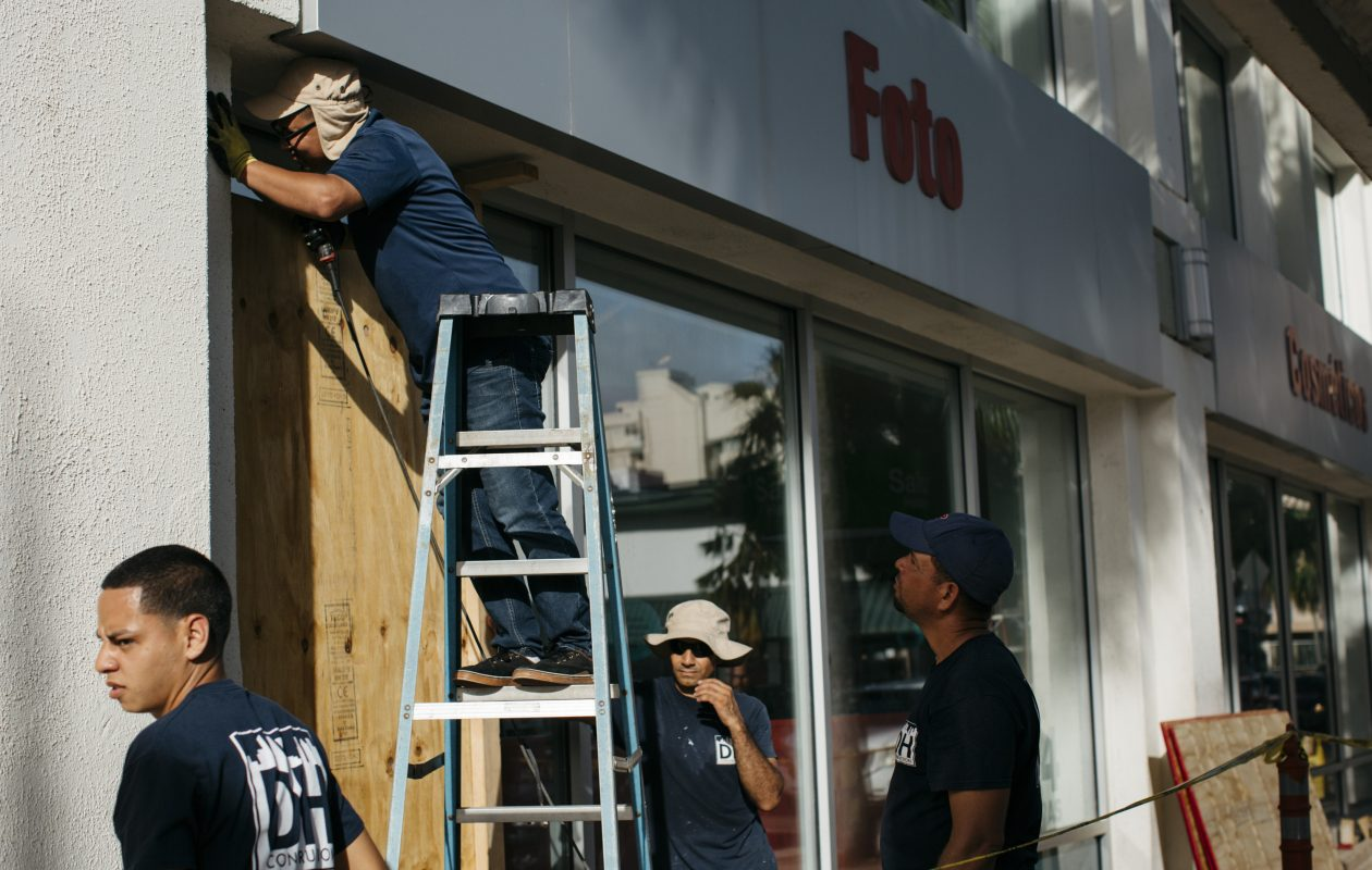 """Workers cover windows at a CVS pharmacy in a tourist area of San Juan, Puerto Rico, Sept. 18, 2017. Hurricane Maria, what the National Hurricane Center called a """"potentially catastrophic Category 5 hurricane,"""" raced towards Puerto Rico and the already-pummeled British and U.S. Virgin Islands on Monday. (Erika P. Rodriguez/The New York Times)"""