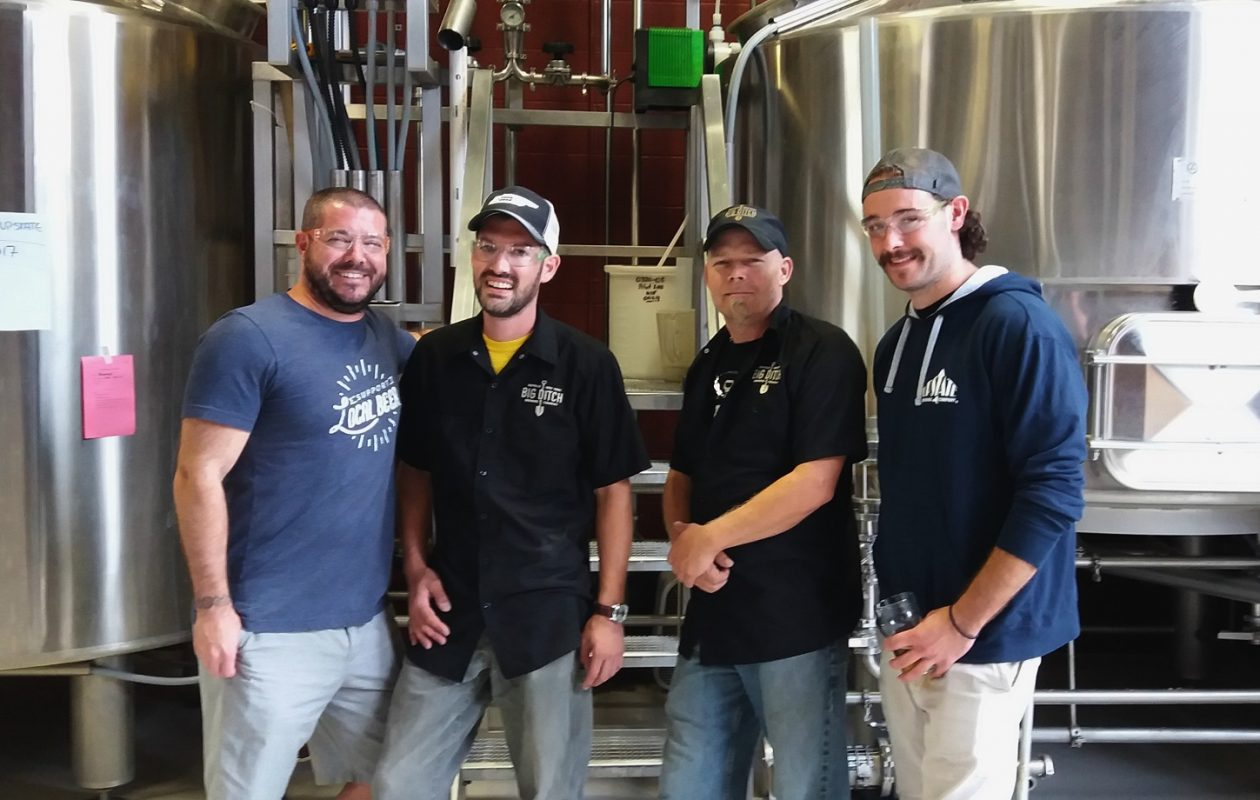 Big Ditch workers, in black, pose with Upstate Brewing representatives. (via Big Ditch)