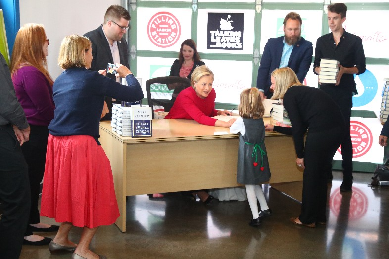 Hillary Clinton greets Cameron Kresse and her mother Melissa at a book signing in Larkinville's Filling Station restaurant on Thursday. (John Hickey/Buffalo News)
