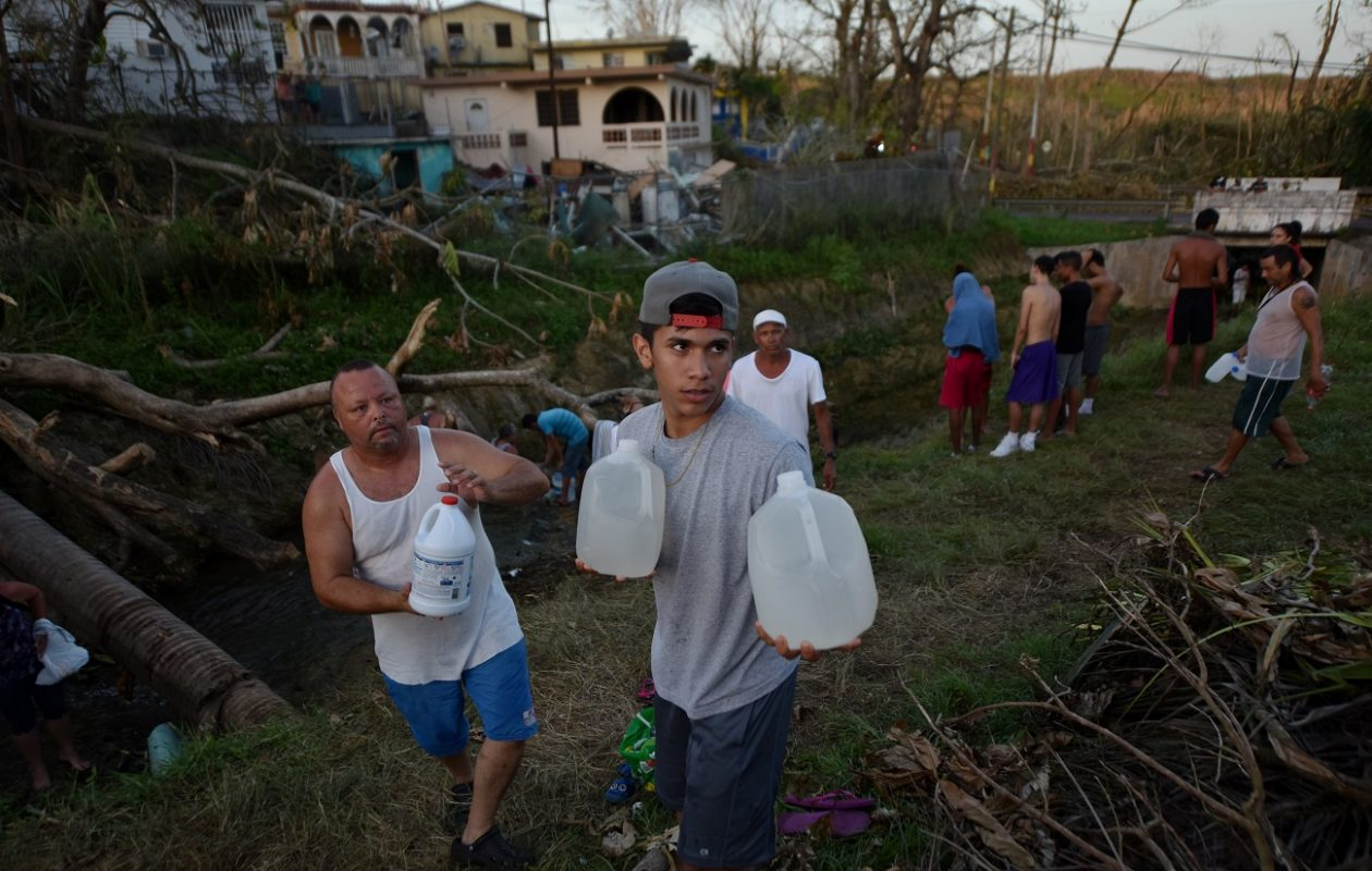 People carry water in bottles retrieved from a canal due to lack of water following passage of Hurricane Maria, in Toa Alta, Puerto Rico, on September 25, 2017.(Hector Retamal/Getty Images)