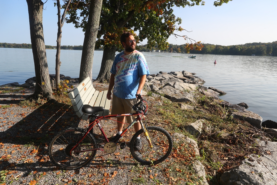 Alex Reinbolt of Bemus Point, rode his bicycle out to the point at Long Point State Park on Chautauqua Lake. Waves from boat wakes and storms is resulting in significant erosion.  (John Hickey/Buffalo News)